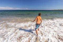 Junge, der durch das Wasser am Strand läuft Lizenzfreies Stockbild