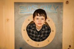 Junge, der durch die Öffnung schaut Stockbilder