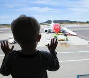 Junge, der durch ein Fenster dem Flughafen betrachtet lizenzfreies stockfoto