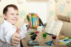 Junge, der durch ein Mikroskop schaut Stockbilder