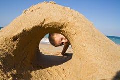 Junge, der durch ein Sandschloß auf dem Strand schaut Lizenzfreies Stockbild