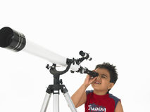 Junge, der durch ein Teleskop schaut Stockfotografie