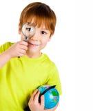 Junge, der durch ein Vergrößerungsglas schaut stockbild