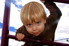 Junge, der durch eine Spielplatzleiter schaut Stockfotografie