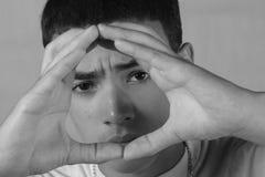 Junge, der durch Hände schaut Lizenzfreie Stockfotografie