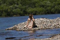 Junge, der durch See sich entspannt Stockbild