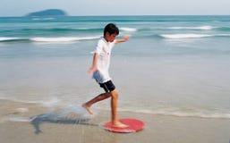 Junge, der durch Wellen surft lizenzfreies stockbild