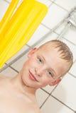 Junge in der Dusche, die Paddel vom Boot hält Stockfotografie