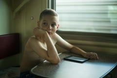 Junge, der e-Buch auf Zug-Reise liest stockbild