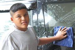 Junge, der ein Auto wäscht Stockbild