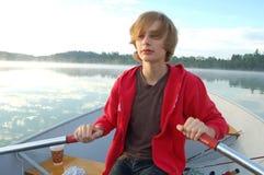 Junge, der ein Boot rudert Lizenzfreie Stockbilder