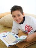Junge, der ein Buch auf dem Fußboden liest Stockfotografie