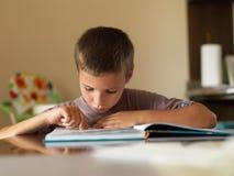Junge, der ein Buch beim bei Tisch sitzen zu Hause liest Stockbild