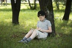 Junge, der ein Buch im Garten liest Stockbild