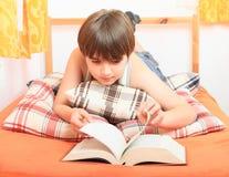 Junge, der ein Buch liest Stockbild
