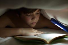 Junge, der ein Buch unter der Decke oder der Steppdecke liest Stockbild