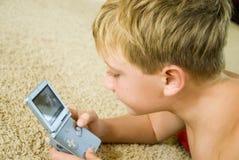 Junge, der ein Computer-Spiel spielt Stockbild