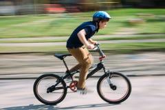 Junge, der ein Fahrrad in einem Park reitet Stockbilder