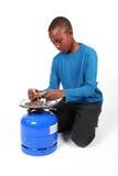 Junge, der ein Feuer auf Gasflasche beleuchtet Stockbilder