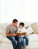 Junge, der ein Fotoalbum mit seinem Vater betrachtet Lizenzfreie Stockfotos