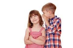 Junge, der ein geheimes kleines Mädchen flüstert Lizenzfreies Stockfoto