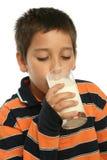 Junge, der ein Glas Milch trinkt lizenzfreie stockfotos