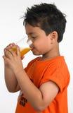Junge, der ein Glas Saft trinkt Stockfotos