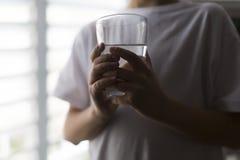 Junge, der ein Glas Wasser, Nahaufnahme hält Lizenzfreie Stockfotografie