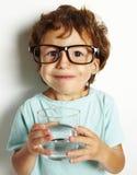 Junge, der ein Glas Wasser trinkt Stockbild