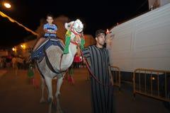Junge, der ein Kamel reitet Lizenzfreie Stockfotos