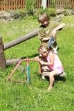 Junge, der ein Mädchen mit Wasser pooring ist Stockbild