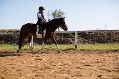 Junge, der ein Pferd in der Ranch reitet stockfotografie