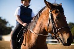 Junge, der ein Pferd in der Ranch reitet lizenzfreies stockbild
