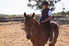 Junge, der ein Pferd in der Ranch reitet lizenzfreie stockfotos