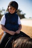 Junge, der ein Pferd in der Ranch reitet stockbilder