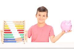 Junge, der ein piggybank gesetzt an einem Tisch mit einem Abakus hält Lizenzfreie Stockfotos