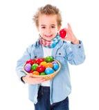 Junge, der ein rotes Osterei zeigt Stockfotos