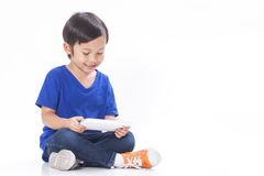 Junge, der ein Spiel auf Computertablette spielt Lizenzfreies Stockbild