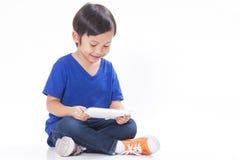 Junge, der ein Spiel auf Computertablette spielt Stockbild