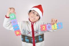 Junge, der ein Zeichen 2014 und 2015 hält Stockbild