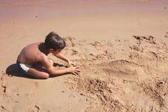Junge, der eine Abbildung auf dem Sand konstruiert. Lizenzfreies Stockbild