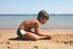 Junge, der eine Abbildung auf dem Strand konstruiert. Stockbild