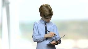 Junge, der eine Anmerkung auf digitaler Tablette macht stock video footage
