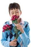 Junge, der eine Blume riecht Lizenzfreie Stockfotos
