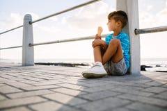 Junge, der eine Eiscreme sitzt nahe Küste isst Stockfoto