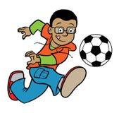 Junge, der eine Fußballkugel tritt Lizenzfreies Stockfoto