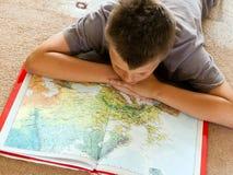 Junge, der eine Karte studiert stockfoto