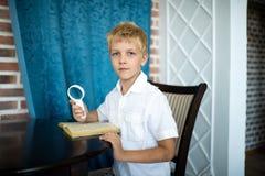 Junge, der eine Lupe hält lizenzfreie stockbilder