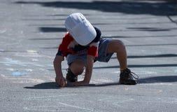Junge, der eine Meldung kreidet Stockfotografie