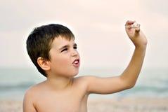 Junge, der eine Muschel auf einem Strand spielt Lizenzfreie Stockfotos